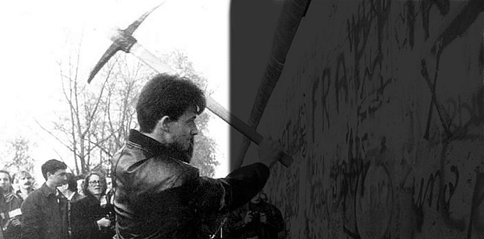 Iconic image of one man with a pick axe chipping away at the Berlin Wall as others look on in support.