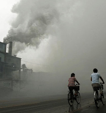 Industrial scene. Factory pouring out pollution. Two humans on bicycles going past.