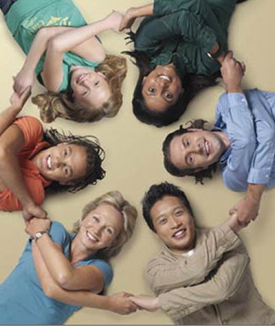 Six humans lying on their backs, seen from above, shoulder to shoulder forming a circle.