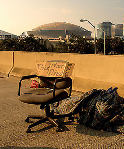 New Orleans after the floods. Office chair outside on street. Body of a dead man wrapped in a blanket lying beside it.